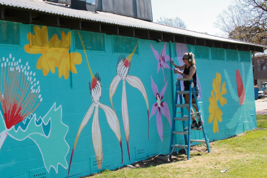 Anya Brock working on the mural outside of the Robinson Netball Centre.