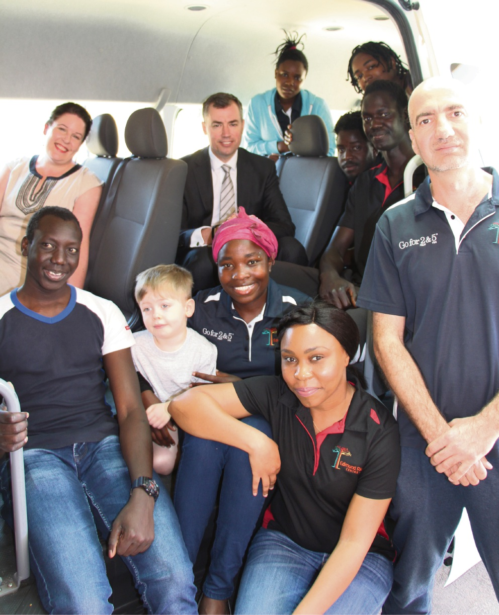 Stirling MHR Michael Keenan inside the bus with Edmund Rice Centre staff and youth leaders including Bella Ndayikeze (middle in the pink bandanna) who had to previously transport all of the players.