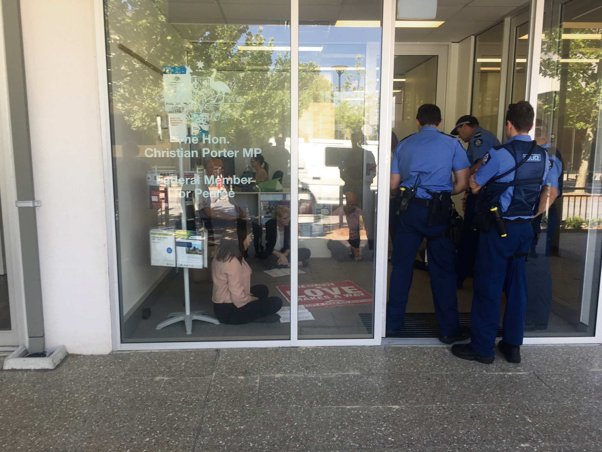 Police move in on the protesters at Christian Porter's Ellenbrook office.