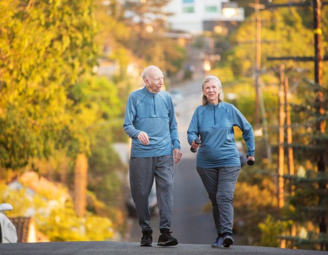 Enthusiastic man and woman with dumbbell weights walking up hill on street