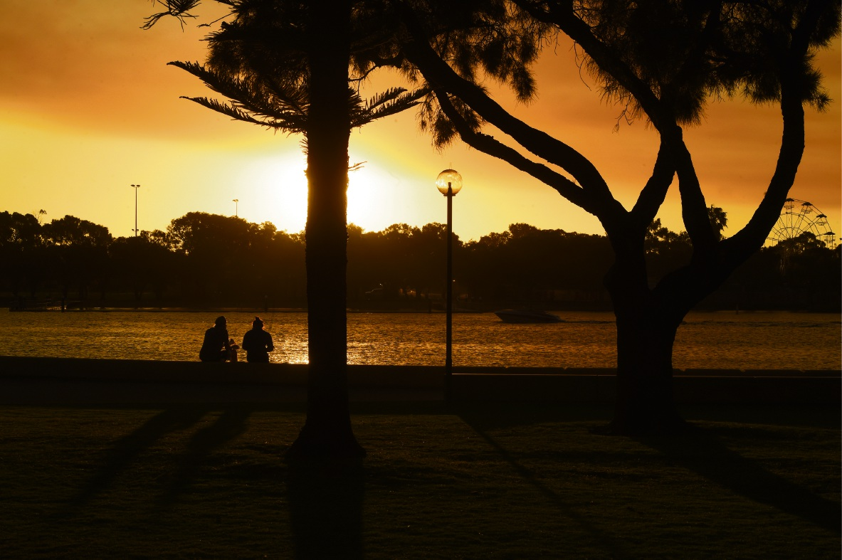 A couple sit on the Mandurah foreshore, watching an amazing sunset with smoke haze from a burn‐off in the hills. Picture: Jon Hewson.