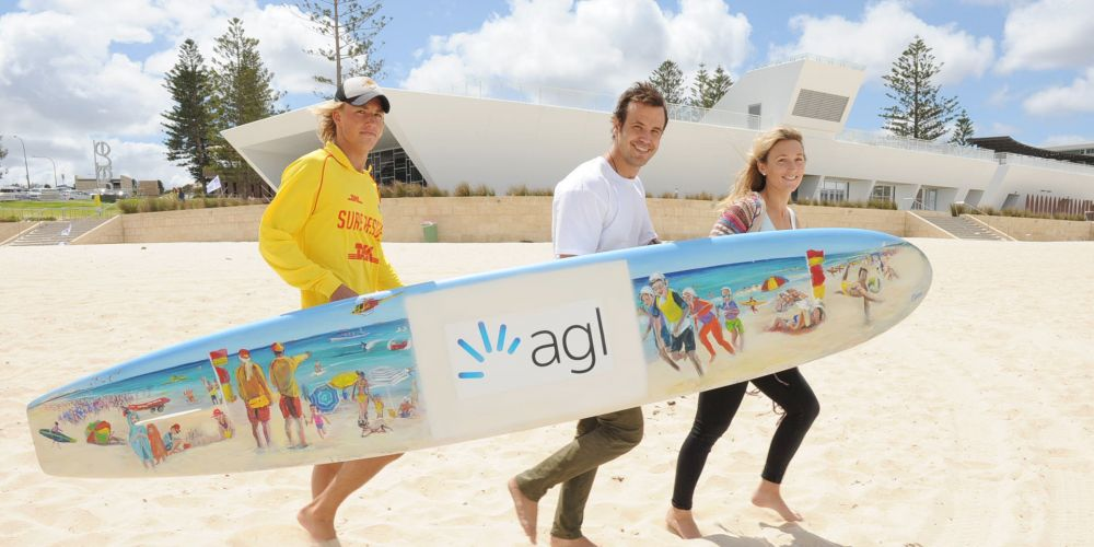 A decorated new board is carried by Mullaloo SLSC's Wes Gould and Hilton artists Jake and Ange Butler at City Beach this morning. Picture: Jon Bassett