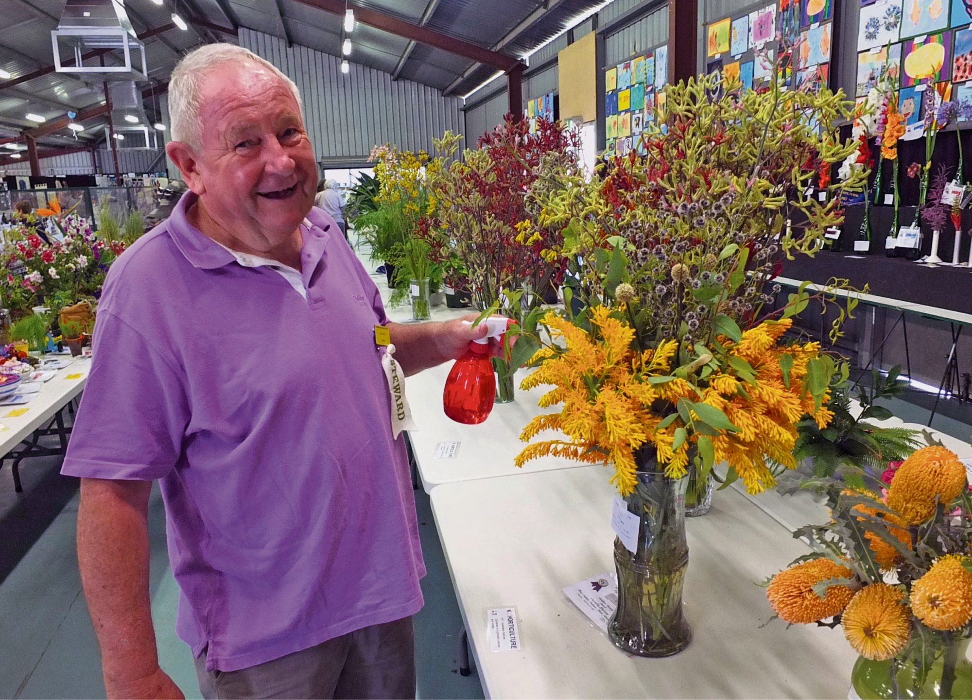 Wanneroo Show steward Eric Coates freshens a horticultural display in the Margaret Cockman Pavilion.