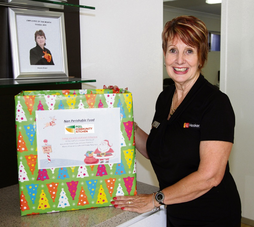Staff member and food drive organiser Jenys Lehmann with the LJ Hooker collection box for The Peel Community Kitchen.