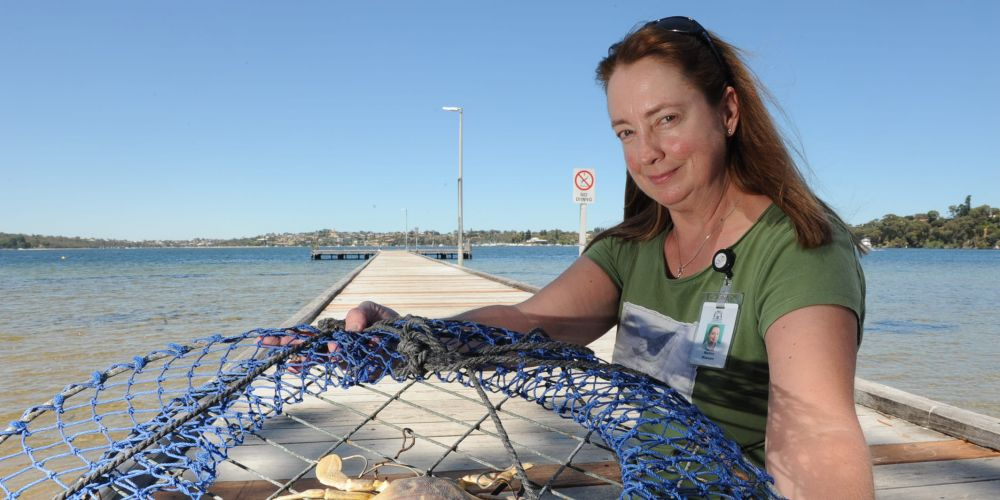 The Department of Fisheries' Marion Massam, with a model of a pest Asian paddle crab, says jetty, shore and boat fishers should any report suspicious crabs this summer. Picture: Jon Bassett.