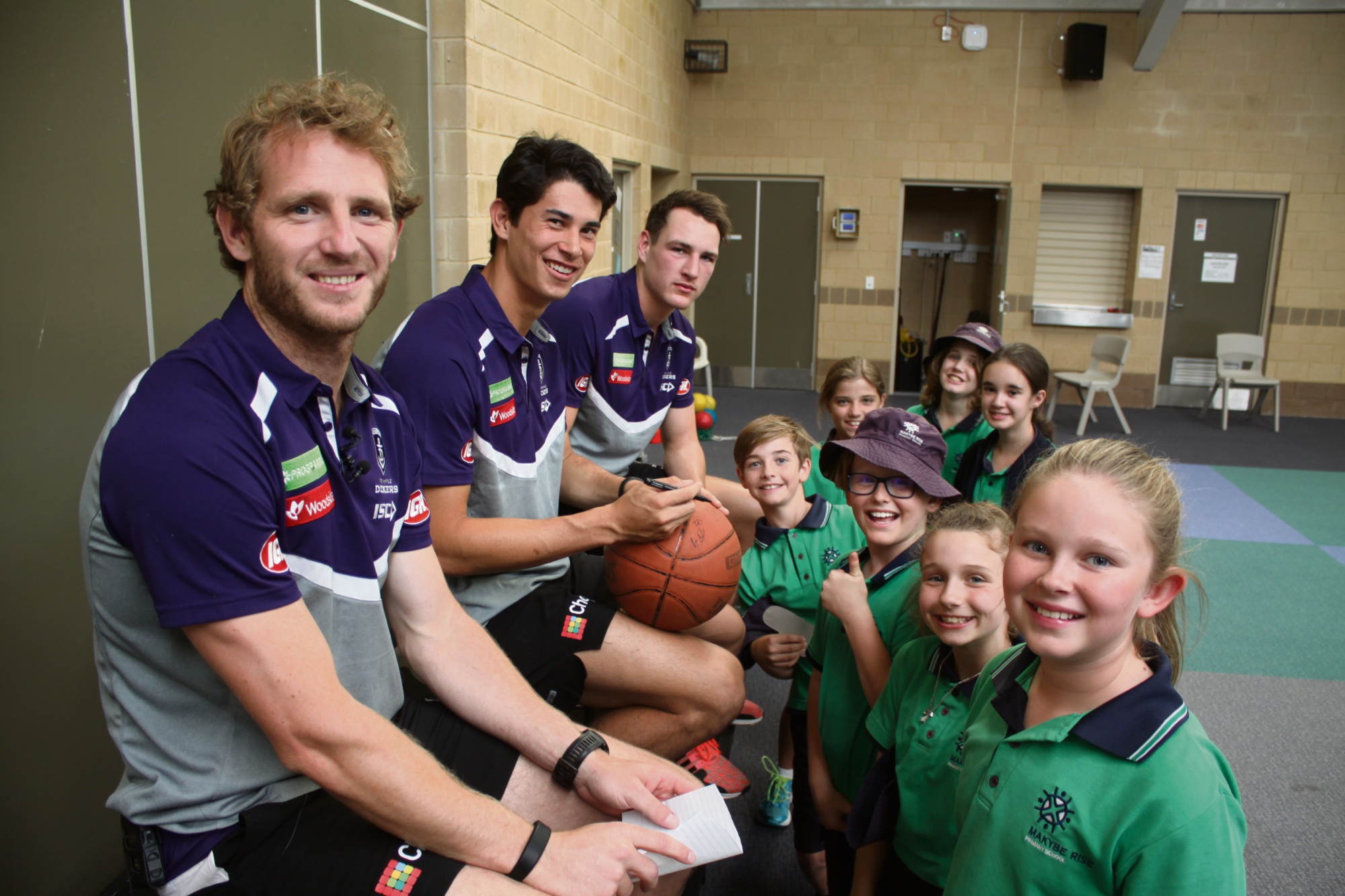 Dockers players Mundy, Banfield and Cox sign autographs for Makybe footy fans.