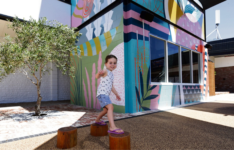 Pippa Buswell (4) plays in front of artwork by Chris Nixon at a redeveloped Melville Plaza, now known as Hawaiian's Melville.
