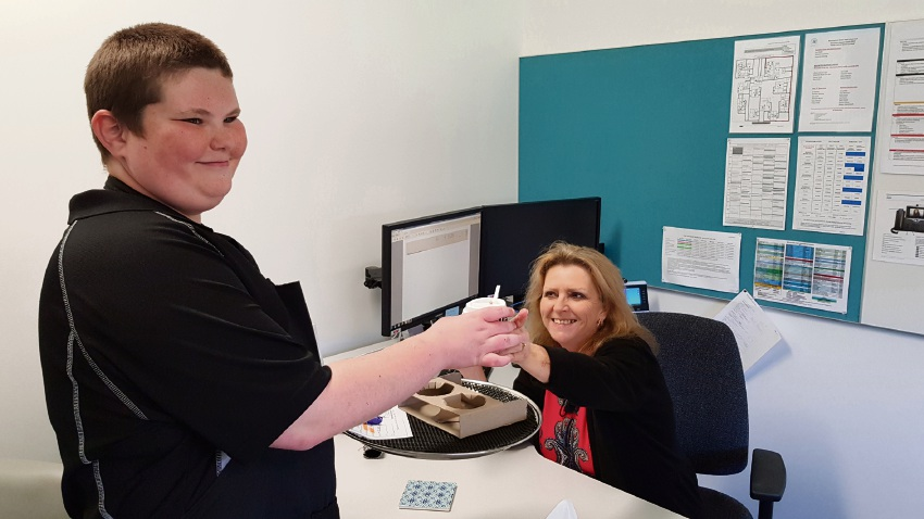 Year 10 Dolphin Cafe Student Jason Bawden delivering coffee to principal Mrs Pippen.