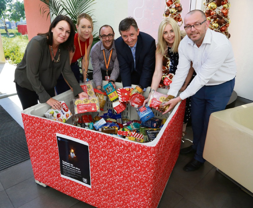 Perth Airport staff with Foodbank WA chief executive Greg Hebble (third from right)  and Perth Aiport staff with some of the donations.