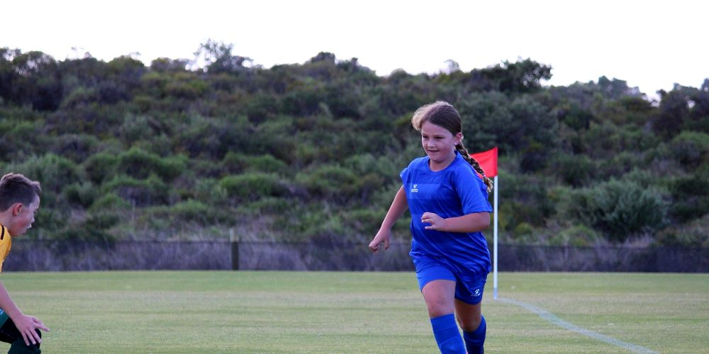 Under-9 team member Tahlia Greasley making a run down the wing in Miniroos.