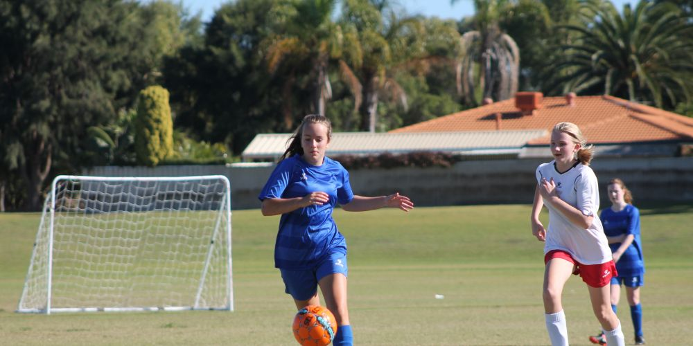 Under-14 Girls League team member Jaymee Lee Mitchell driving the ball out from defence.