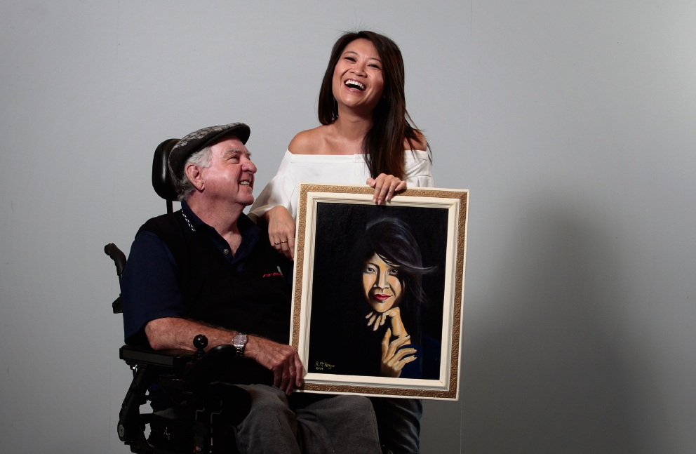 Robert McKenzie (75) has been in a wheelchair for 50 years, and took up painting in retirement. He recently presented his portrait of Tracy Vo to the Channel 9 presenter. Photo: Marie Nirme