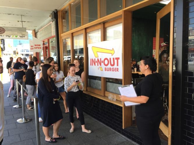 Burger lovers queue at The Bird on William Street for the In-N-Out pop-up store today.