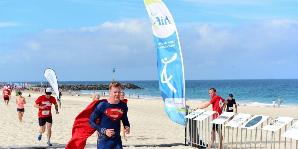 Ian Bassett participating in the Sunshine Beach Run as Superman.