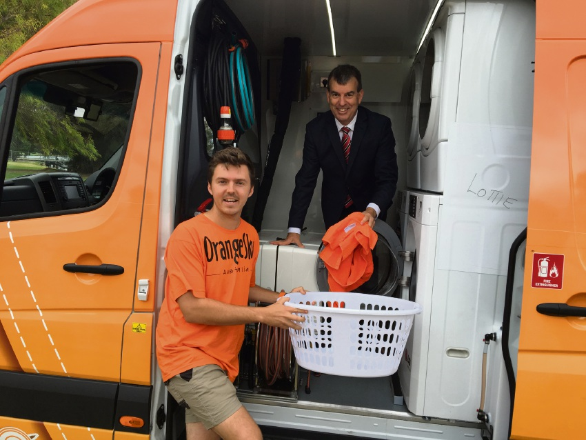 Orange Sky co-founder Nic Marchesi and Water Minister Dave Kelly do some laundry in the van. Picture: Aaron Corlett.
