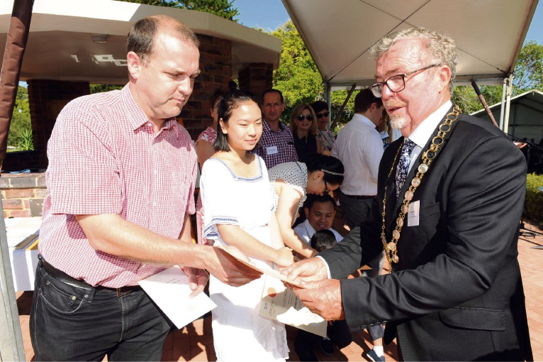 Richard Vokes and Grace Chow get their citizenship certificates from Mosman park Mayor Brett Pollock. Photo: Jon Bassett