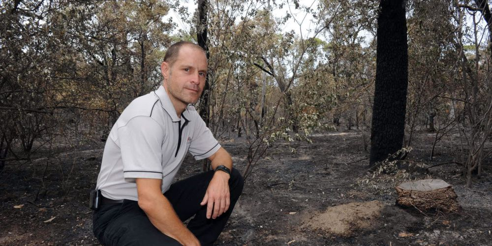 Kings Park biodiversity and conservation manager Steve Easton looks at the damage at the bushfire's starting point. Picture: Jon Bassett