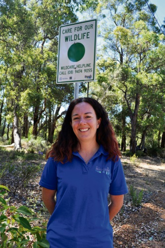 Shire of Mundaring environmental officer Jolene Wallington stands in front of green spot sign on Mundaring Weir Road. Picture: Supplied