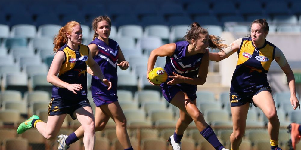 Caption: Parris Laurie, who was best on ground for the Coast team, looks for options as West's Amber Goodwin-Wissink closes in to tackle.