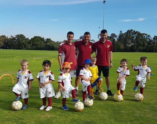 Kicking off with players are coaches (l-r, rear) Adrian Manno, Adi Juric and former Perth Glory player Branko Jelic.