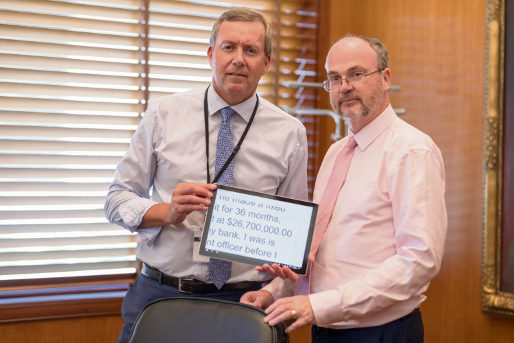 Reece Whitby, holding a copy of the scam message he received, with Bill Johnston.