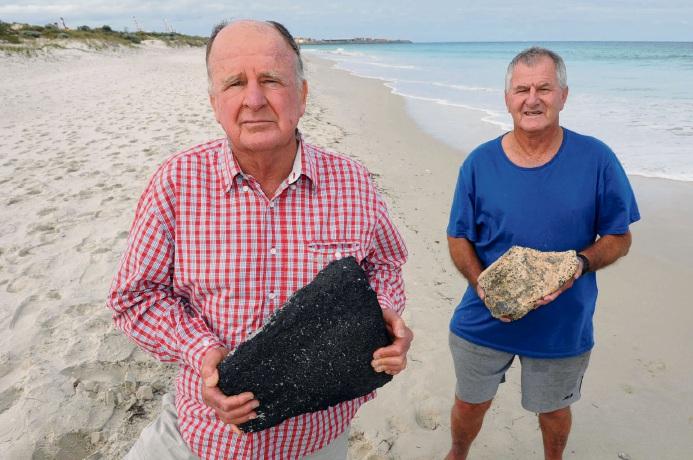 Daily beach walkers (l-r) Paul Gabbedy holds bitumen, and Peter McLarty a limestone rock, allegedly among Port Beach debris heading to Mosman Beach. Picture: Jon Bassett