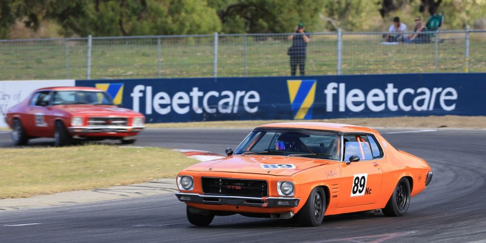 John Bondi won the Historic Touring Cars in his orange Monaro from his brother Brian Bondi in a red Monaro. Picture: Barnsiesphotos