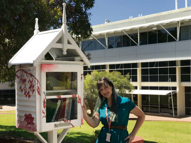 Librarian Tamara Capper stocking one of two Little Free Library boxes installed at Murdoch University.