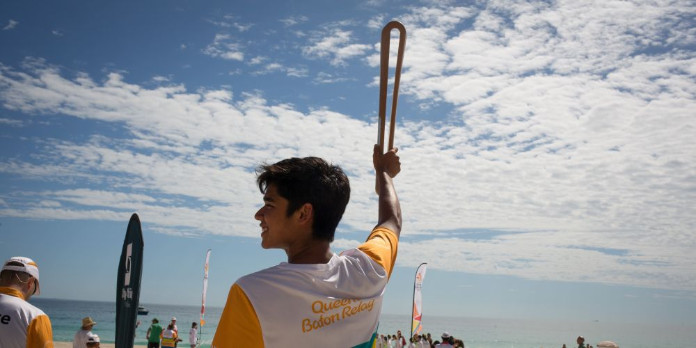 The Queen's Baton, carried by batonbearer Rahul Jegatheva, on Scarborough Beach.