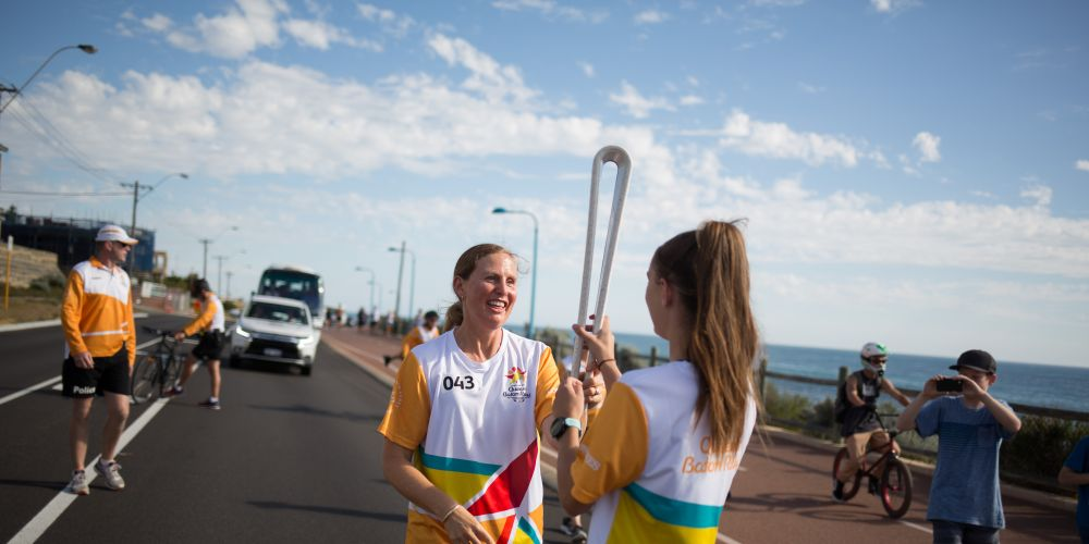 The Queen's Baton, carried by batonbearer Lisa MacNeill handing over to batonbearer Olivia Roberts.
