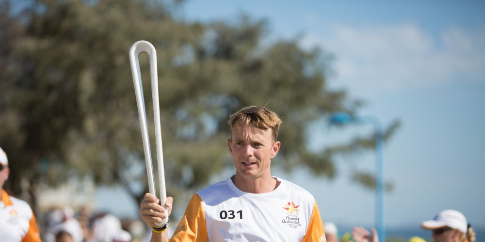 The Queen's Baton, carried by batonbearer Daniel Humble, on West Coast Drive.