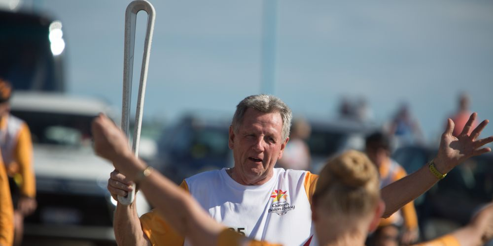 The Queen's Baton, carried by batonbearer Noel Patterson handing over to batonbearer Norma Beer.
