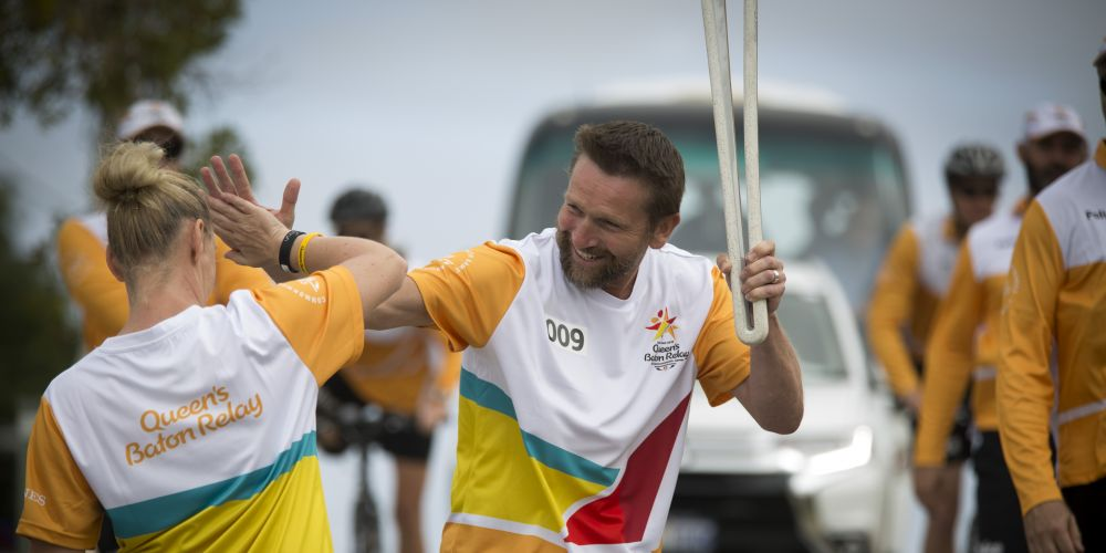 Batonbearer Richard Furber (left) passing the baton to Shirley Treasure as the Queen's Baton Relay visited Quinns Rocks. Picture: Supplied