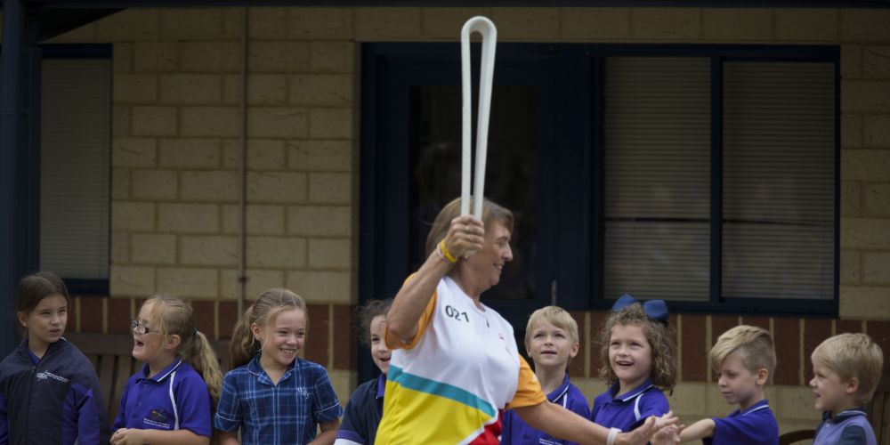 Baton bearer Helen Orzel carrying the baton through Wanneroo Primary School as the Queen's Baton Relay visited Wanneroo.  Picture: Supplied