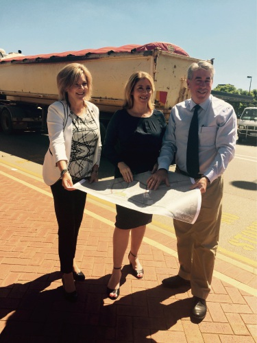 Murray MLA Robyn Clarke, Transport Minister Rita Saffioti and Shire of Murray President David Bolt study plans for the deviation that will remove trucks like the vehicle in the background from Pinjarra's main street.