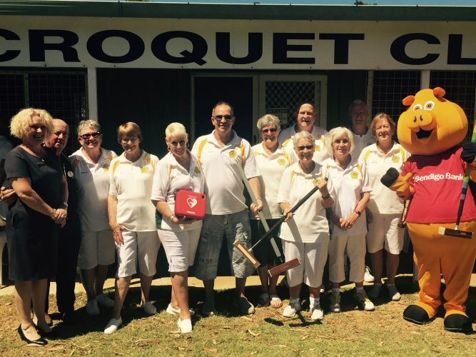 Halls Head and Lions Club Croquet Clubs members with bank mascot Piggy and the defibrillator machine.