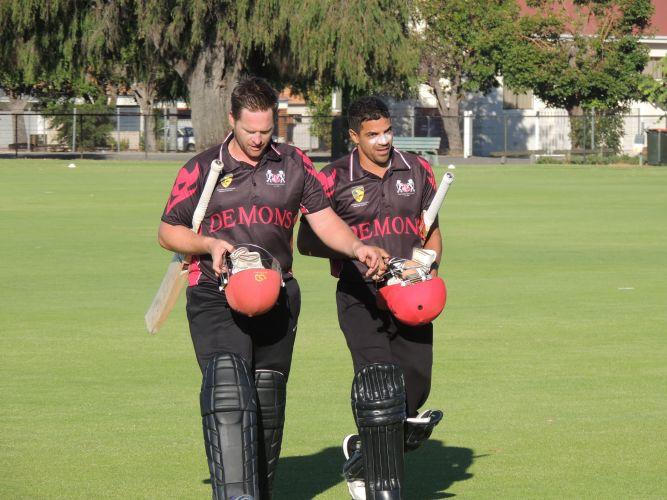 Perth batsmen Luke Jury and Jacob Van Galen walk off after securing victory.