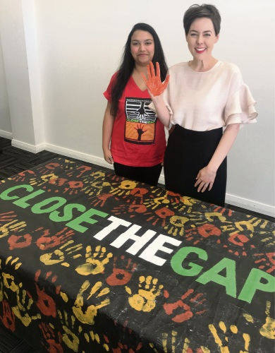 Oxfam supporter Nikita Nayar and Belmont MLA Cassie Rowe in front of the Close the Gap banner.