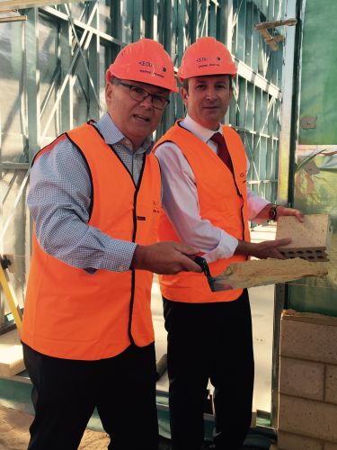 Premier Mark McGowan and Mandurah MLA David Templeman have a crack at brick laying at the Lakelands High School site.