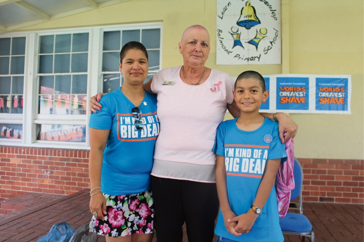 Belmont Primary School principal Stephanne Dann, middle, appreciates the efforts of Gina Kyaw Maung and Jack Escobar, 10, after they shaved their heads.