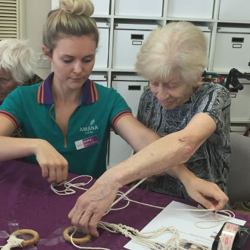 Therapy assistant Aroha teaches Jean about macrame.