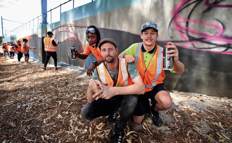 Mural artist Drew Straker (centre) with Buzoya Bucumi and Ben D'Souza of Thornlie and other Kensington PCYC Leadership Program members. Pictures: David Baylis d480807