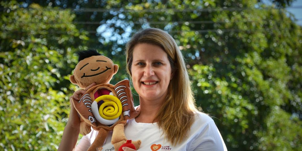 480585 - Shelly Skinner with Roy - a doll that helps answer some of the medical questions children at the camp may have regarding their experience.