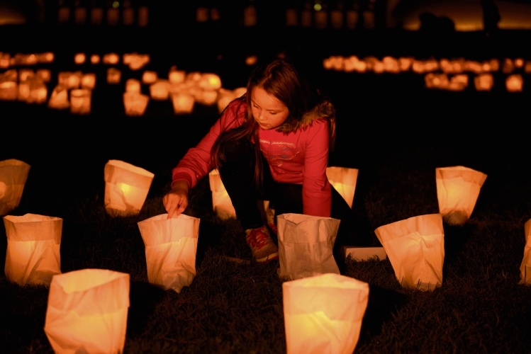 Earth Hour Night 2014: A young girl lighting a candle at the Candle Installation by Jorge Pujol on the lawns of Australian Parliament House in Canberra. Photo by Michael Mulrine / WWF-Aus