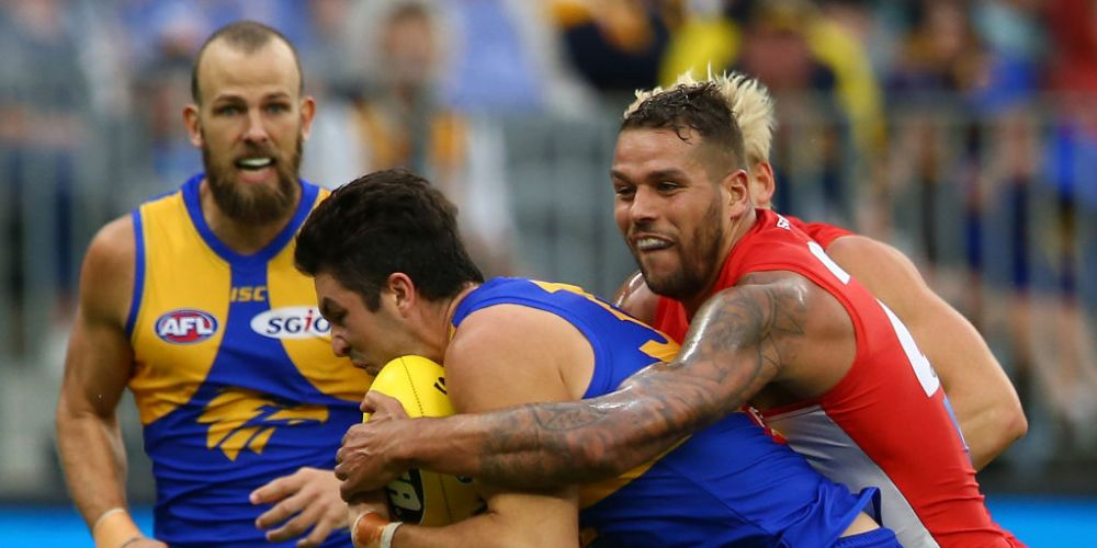Lance Franklin lays a tackle on West Coast backman Tom Barrass. Photo: Getty