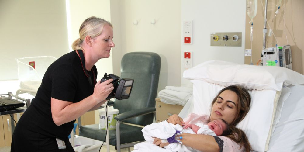 Dr Cathryn Poulton with Sofia Akram being held by mother Valda