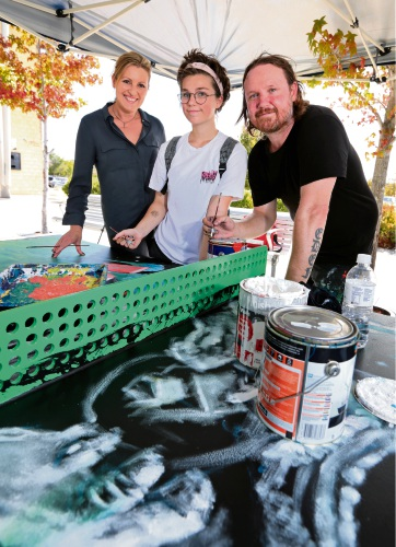 Cr Cate McCullough, Alisha Thomas, of Ellenbrook, and street artist Steve Browne painting one of the ping pong tables.  Picture: David Baylis www.communitypix.com.au   d480935