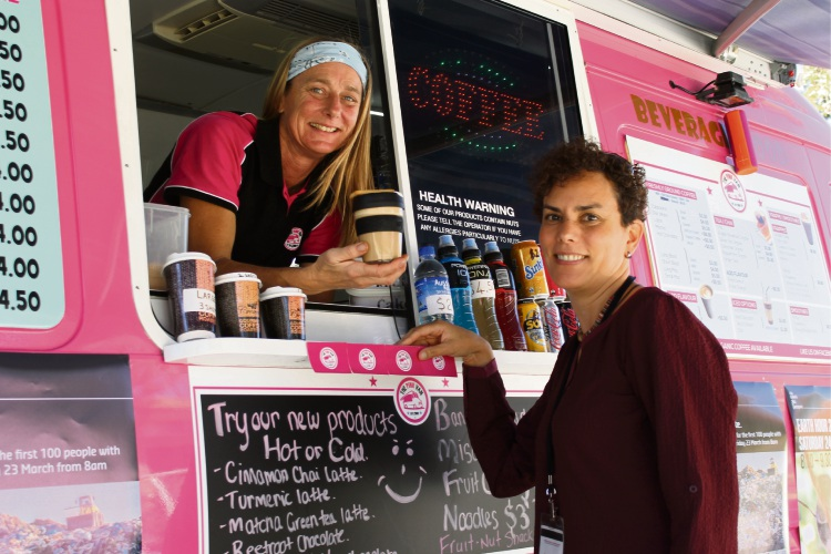 The Pink Van owner Lexie Goerling, of Attadale, hands a free coffee to Curtin University's properties, facilities and development planning director Rocio Bona, of Shelley, during Earth Hour celebrations.
