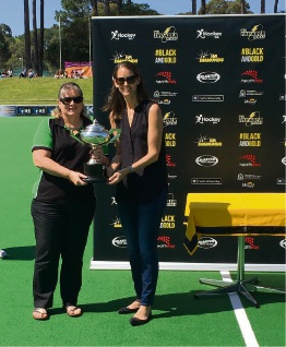 Harlies club president Diana Fuller, accepting an award from a Hockey WA representative at the Perth Hockey Stadium. Credit: Daniel Carson