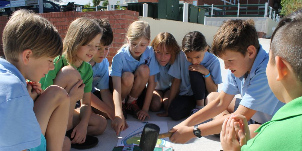 A group of Bayswater Primary School students placing the Historical Heartbeat sticker at the school. Picture: Keith Clements